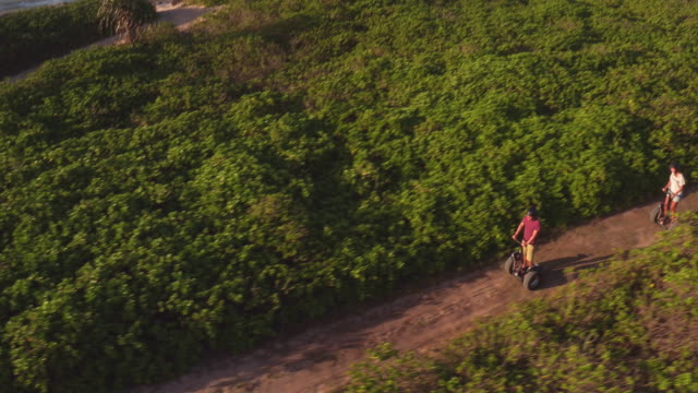 high-angle drone shot panning over group riding segways - turtle bay hawaii stock videos and b-roll footage
