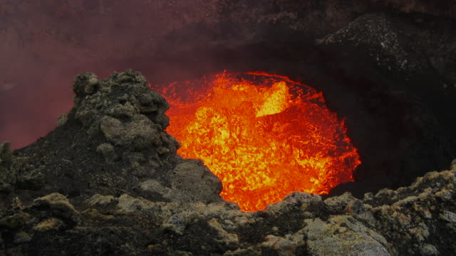 high-angle handheld shot of a lava lake in a crater on ambrym, vanuatu [filmed at 50fps and maintained at half speed]. - lava stock-videos und b-roll-filmmaterial