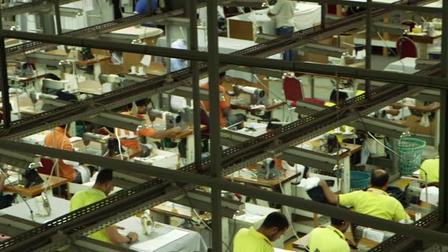 high-angle mcu pan-right across a garment factory shop floor. - maßkonfektion stock-videos und b-roll-filmmaterial