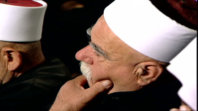 high-angle of a druze sheikh wearing an amamah or turban at a community meeting. turbans and dark attire indicate that he is an uqqal, meaning... - turban stock videos & royalty-free footage