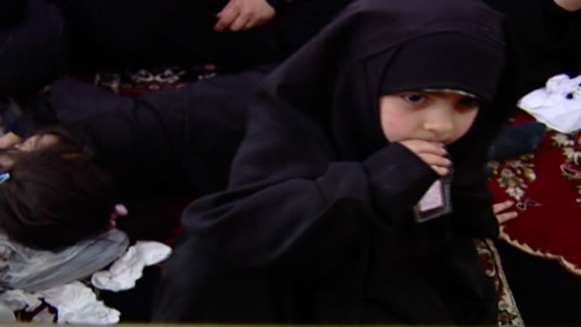 highangle cu on a bored little shia girl in chador during ashura which is a mourning rite commemorating the death of hussain ibn ali organised by... - religiöse kleidung stock-videos und b-roll-filmmaterial