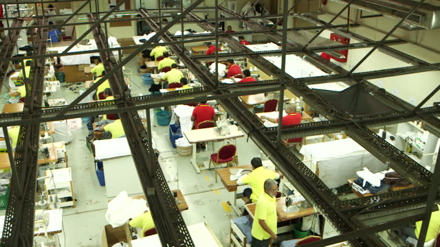 high-angle pan-left across a garment factory shop floor. - tailored clothing stock videos & royalty-free footage