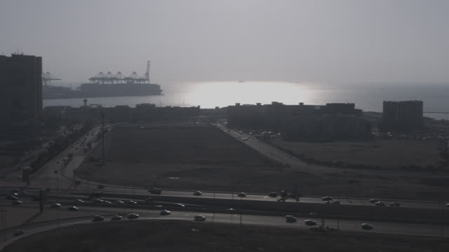 high-angle pan-left to a view of port area on the red sea coast of jeddah at dusk. - jiddah stock videos & royalty-free footage
