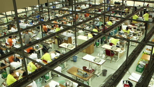 high-angle pan-right across a garment factory shop floor. - jiddah stock videos & royalty-free footage