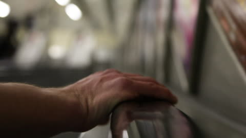 stockvideo's en b-roll-footage met high-angle sequence showing the hand of a person travelling downwards on an empty escalator inside a tube station, london, uk. - veiligheidshek
