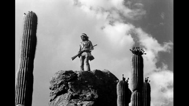 vídeos y material grabado en eventos de stock de highangle shot looking up at actor playing native american warrior squatting on cliff looking right and left rising and then running off rear of... - cultura indio americano