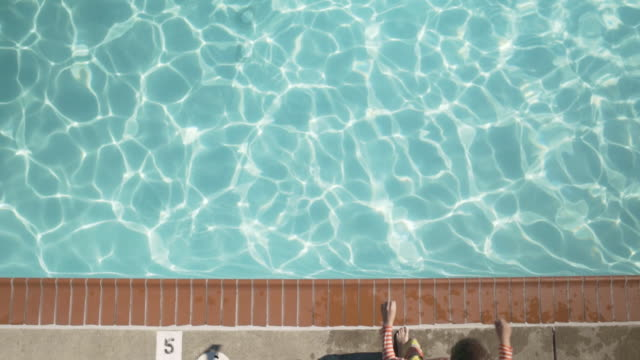 vidéos et rushes de high-angle shot of a boy jumping into a pool - dessus