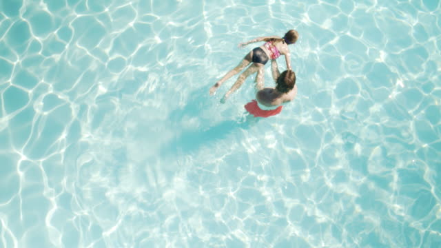 High-angle shot of a father teaching daughter to swim
