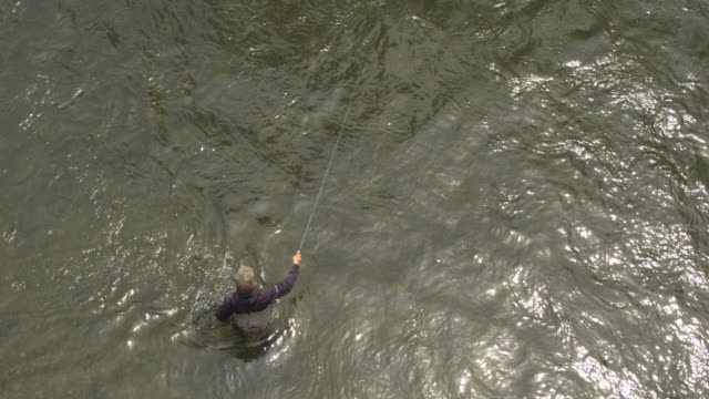 High-angle shot of a fisherman standing in a river