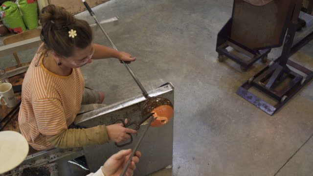 High-angle shot of a woman shaping molten glass