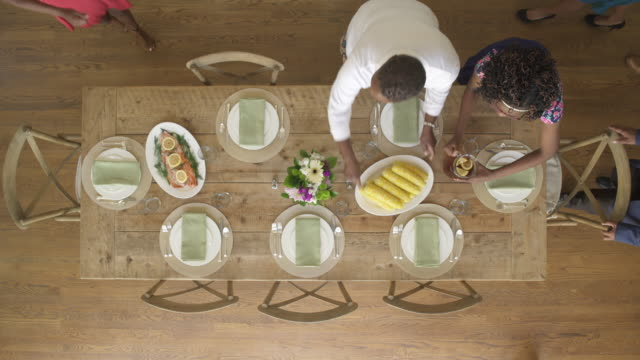 High-angle shot of family members placing food on a table