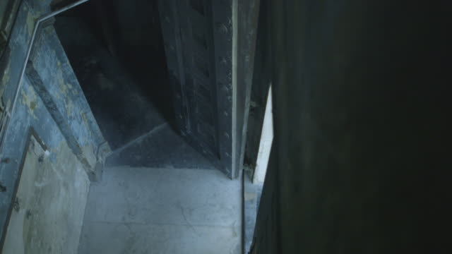 High-angle shot showing a gloomy vestibule in a dilapidated church, UK.