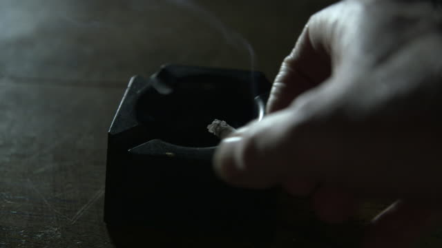 high-angle view of a cigarette being stubbed out in an ashtray on a wooden table. - smoke physical structure stock videos & royalty-free footage
