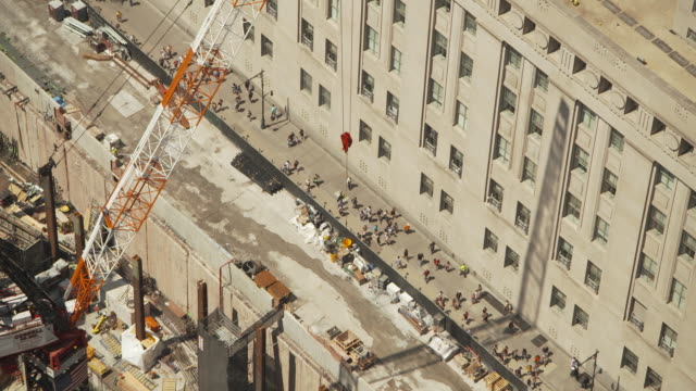 High-angle view of a crane protruding from the edge of the construction site for the new World Trade Center as people walk below, Manhattan, New York City, USA, summer 2011.