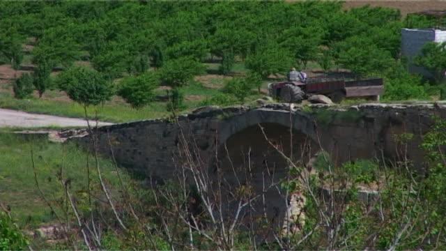 vídeos y material grabado en eventos de stock de high-angle view of a tractor on a bridge over the sabun suyu river a tributary of the afrin river, in the aleppo governorate. - huerta