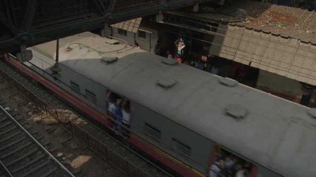 High-angle view of a train accelerating out of Wadala Road Station in Mumbai, Maharashtra, India.
