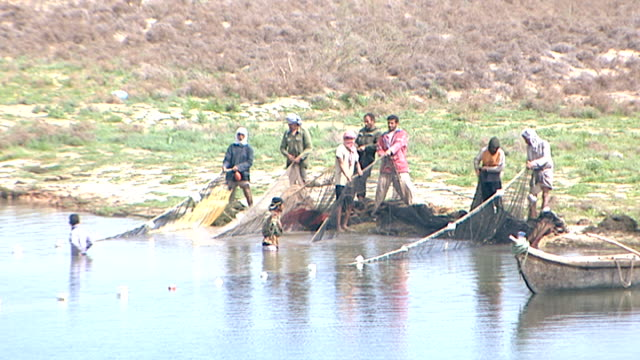 high-angle view of fishermen with nets on the shores of the shatt al-arab. the river is formed by the confluence of the euphrates and tigris and runs... - basra stock videos & royalty-free footage