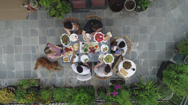 high-angle view of friends gathered for dinner - patio stock videos & royalty-free footage