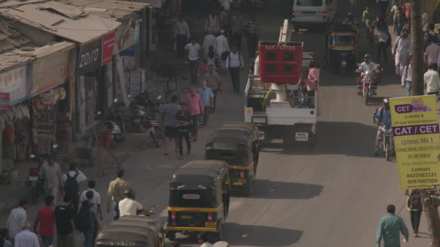high-angle view of people and traffic on a street in mumbai, maharashtra, india. - jinrikisha stock-videos und b-roll-filmmaterial