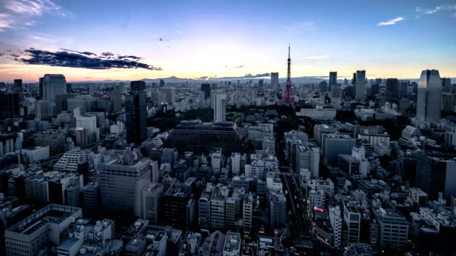 high-angle view of tokyo skyline from day to night, viewing tokyo tower and city streets, with sun setting behind the sketch of mt. fuji - horizont über land stock-videos und b-roll-filmmaterial