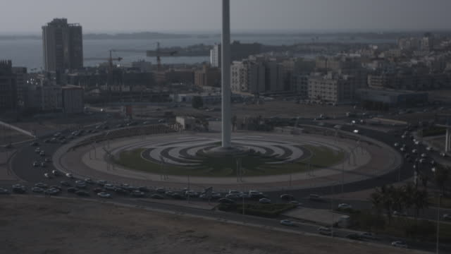 high-angle view of traffic around the tallest flagpole in the world standing on king abdullah square roundabout in jeddah. - jiddah点の映像素材/bロール