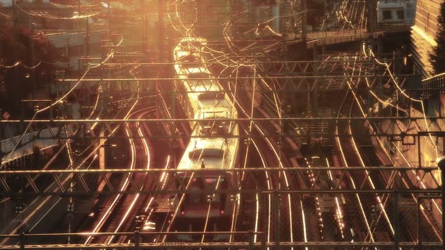 vidéos et rushes de high-angle view of two opposite subway trains winding pass each other at sunset, ookayama (大岡山), tokyo, japan - chemin de fer