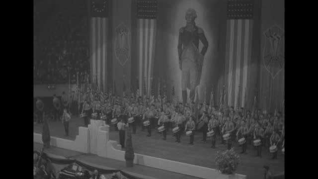 high-angle views conductor with large baton directs drum corps and military band on stage during the german-american bund rally at madison square... - newsreel stock videos & royalty-free footage