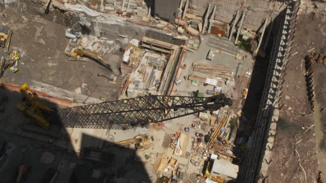 high-angle wide shot of a crane moving across the foundations for one of the new world trade center buildings, summer 2011, new york city, usa. - tribeca stock videos & royalty-free footage