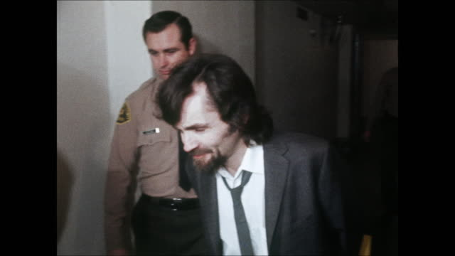 high-definition video footage of a smirking charles manson, wearing handcuffs and a suit and tie. manson addresses press photographers, while he is... - 殺人者点の映像素材/bロール