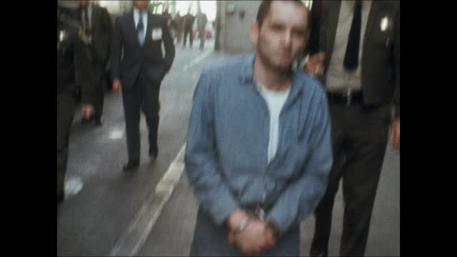 highdefinition video footage of charles manson in a prison jumpsuit handcuffs and ankle shackles police escort him off a bus and down a sidewalk - crime or recreational drug or prison or legal trial stock videos & royalty-free footage