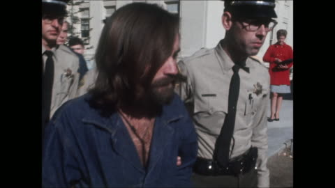 high-definition video footage of charles manson in handcuffs and a denim prison jumpsuit, being escorted outside of a courthouse by police officers. - crime or recreational drug or prison or legal trial stock videos & royalty-free footage