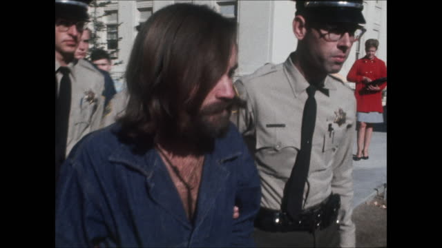 high-definition video footage of charles manson in handcuffs and a denim prison jumpsuit, being escorted outside of a courthouse by police officers. - crime or recreational drug or prison or legal trial stock-videos und b-roll-filmmaterial