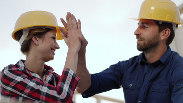 High-five! Female architect celebratory hit the palm of foreman hand
