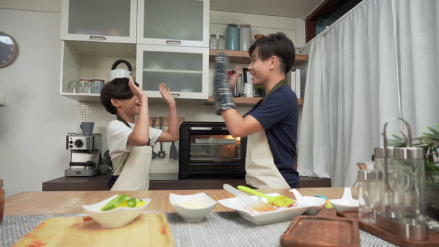high-five to success for making pizza by asian big brother, the little brother having a fun activity to put pizza decorated with ham to baking in the oven for dinner. concept of asian family with two children, son sibling cooking food. - 14 15 years stock videos & royalty-free footage