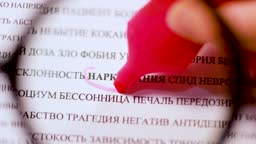 Highlighting the word Addiction in an Russian newspaper with a pink marker, top view through a magnifying glass. Bad habits, drug addiction