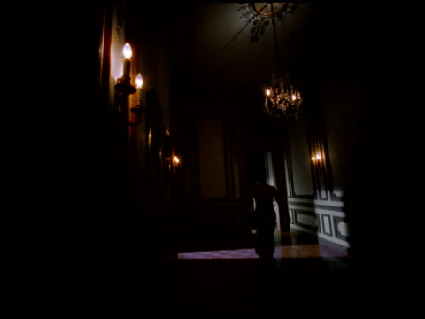 Highly Stylized SLIGHT CRANE DOWN SLO MO BACK of unidentifiable female fancy halter dress running away from frame down elaborate dimly lit hallway...