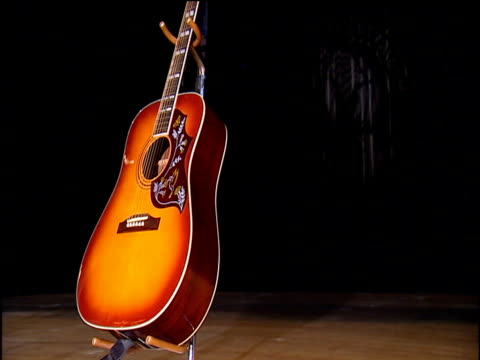 Highlypolished Acoustic Guitar In On Stand In A Spotlight On