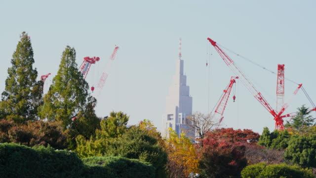 high–rise building stands behind the jingu gaien trees in shinjuku ward from jingu gaien, chhiyoda ward, tokyo japan on november 19 2017. many construction cranes work for build the new national stadium of tokyo olympic 2020. - オリンピック大会点の映像素材/bロール