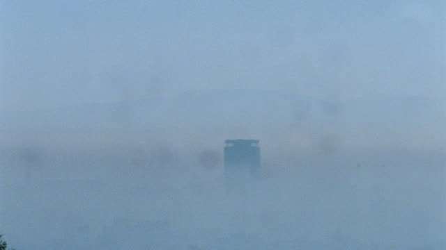 vidéos et rushes de high-rise sticking out of thick smog, fog. note: fingerprints on lens. - smog