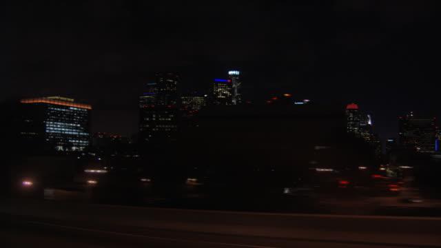 High-speed drive past Los Angeles high-rises at night, passenger POV