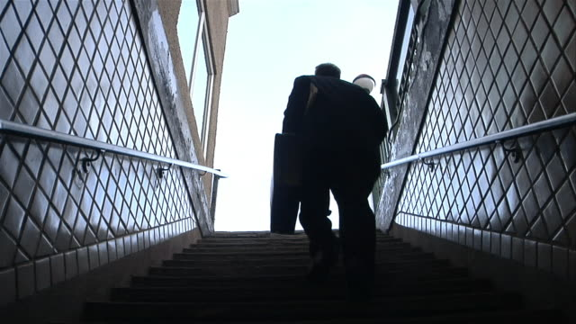high-speed low angle shot of male professional running up stairs and leaving subway station - staircase stock-videos und b-roll-filmmaterial