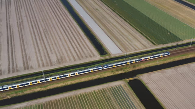 stockvideo's en b-roll-footage met high-speed train crossing agricultural fields seen from an aerial perspective, netherlands - nederland