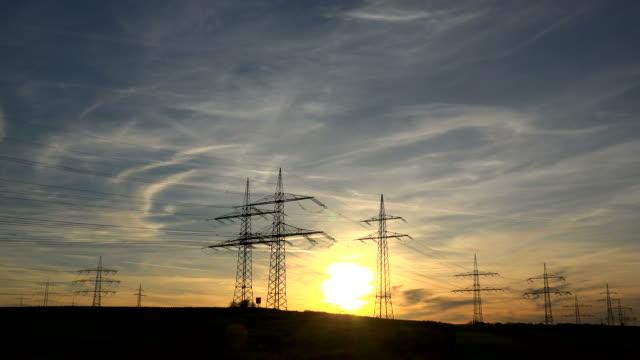 high-voltage overhead lines at sunset - hochspannungsmast stock-videos und b-roll-filmmaterial