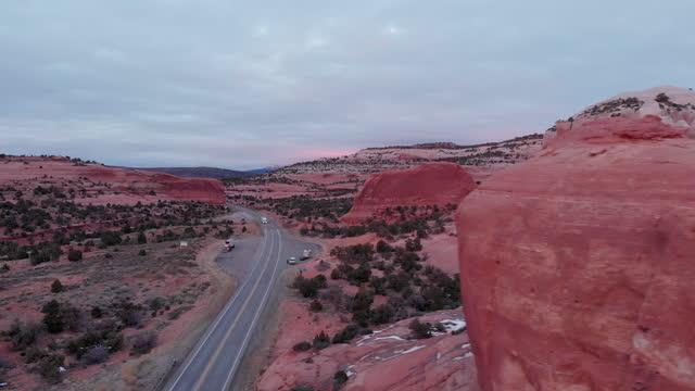 highway 191 bei moab, utah bei sonnenuntergang mit der berühmten sandsteinfelsenformation wilson arch, als semi trucks, die die haupt-lkw-route mit fracht befördern - moab utah stock-videos und b-roll-filmmaterial