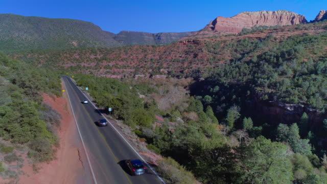 vidéos et rushes de route 89a entre les montagnes à sedona, arizona. drone vidéo avec le mouvement de la caméra descendante. - sedona