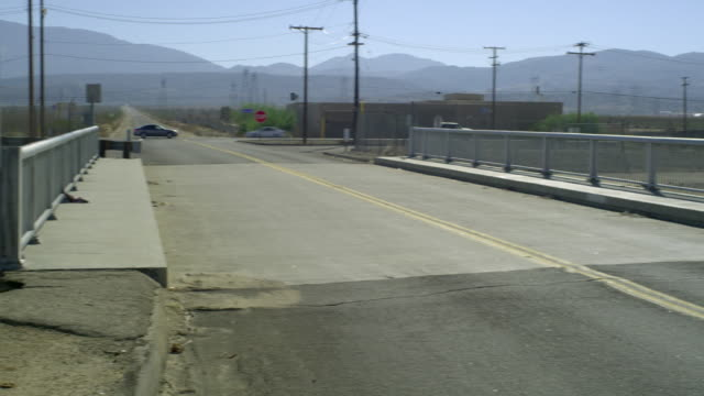 ws pan highway crossing canal with hills in background, palmdale, california, usa - palmdale stock videos and b-roll footage