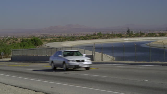 ws pan highway crossing canal with mountains in background, palmdale, california, usa - palmdale stock videos and b-roll footage