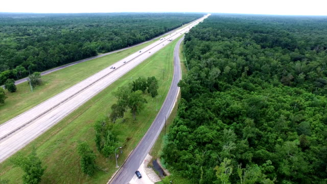 Highway cutting right through a thick Forest Aerial View East Texas
