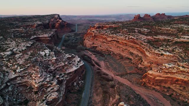 highway cutting through canyon near moab, utah - aerial - moab utah stock-videos und b-roll-filmmaterial
