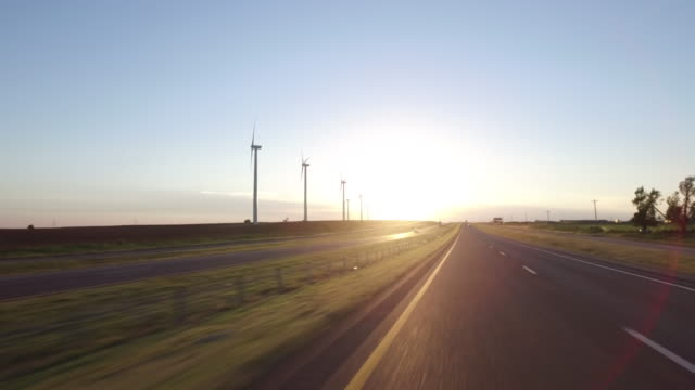 highway driving passing wind turbine at sunset - oklahoma stock-videos und b-roll-filmmaterial